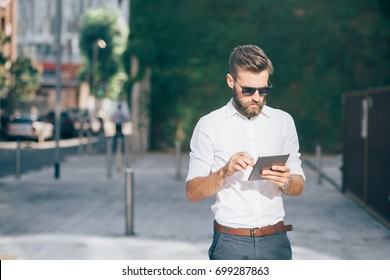 young businessman bearded outdoor using tablet - remote working, technology, communication concept