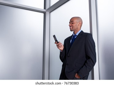 Young businessman beside an office window looking at his cell phone, smiling.