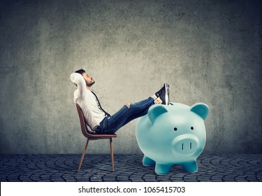 young businessman with big piggy bank relaxing sitting on chair