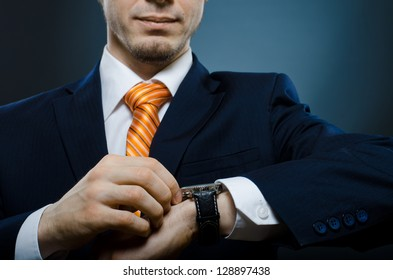 young businessman in black costume wind clock (wristwatch) on hand, closeup
