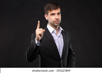 Young businessman in a black suit pointing his finger