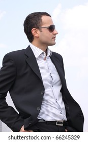 Young businessman in a black suit and sunglasses on sky background