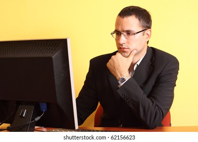 Young businessman in a black suit working on computer at office