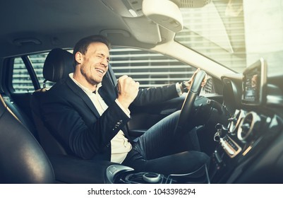 Young businessman in a blazer celebrating success with a fist pump while driving in a car during his morning commute