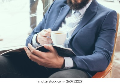 Young businessman in a blue jacket with a cup of coffee, reading a magazine in a cafe
