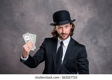 3f31ba5d4db young businessman with bowler hat in black suit showing money