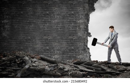 Young businessman breaking old wall with hammer