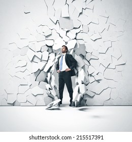 Young businessman breaking trough a concrete wall