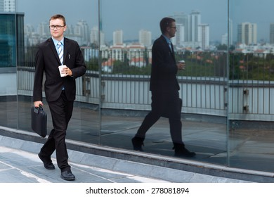 Young businessman with briefcase and coffee cup walking outdoors