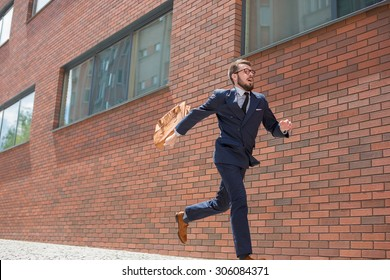 Young businessman with a briefcase and glasses running in a city street on a background of red brick wall