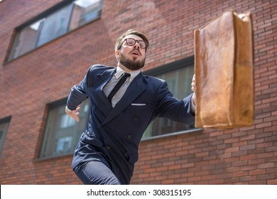 Young businessman with a briefcase and glasses running in a city street on a background of red brick wall. concept of rapid career