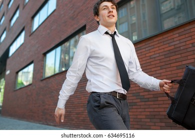 A young businessman with a briefcase in his hand runs to work along the street along the wall of the building. Concept of a rapid career.