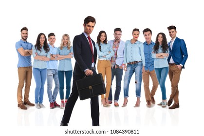 young businessman with briefcase walking in front of his young team on white background while they are standing