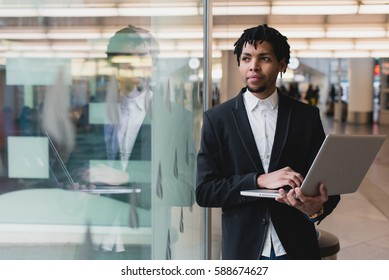 Young businessman browsing a laptop in the airport. Look across the window. Horizontal outdoors sot.
