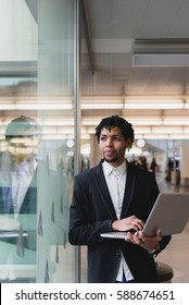 Young businessman browsing a laptop in the airport. Look across the window. Vertical outdoors sot.