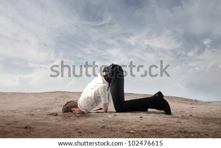 Young businessman burying his head in the sand