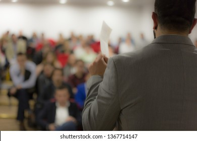 Young businessman at business conference room with public giving presentations. Audience at the conference hall. Entrepreneurship club.