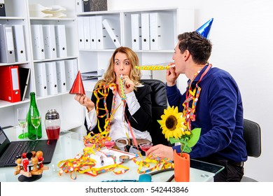 young businessman and businesswoman celebrating together in the office