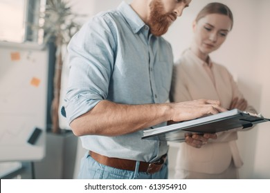 Young businessman and businesswoman discussing new project with clipboard