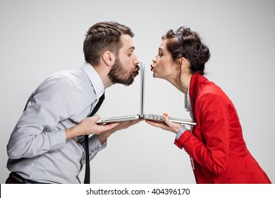 The young businessman and businesswoman with laptops kissing screens on gray background