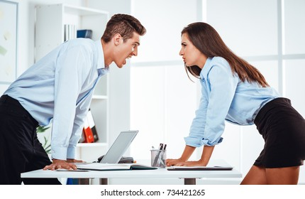 Young businessman and businesswoman staring at each other with hostile expressions. They are have a conflict on a work.