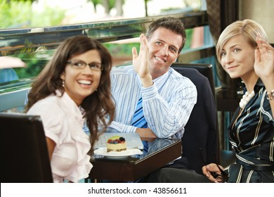 Young businessman and businesswomen having a meeting in cafe, smiling and waving to somebody.