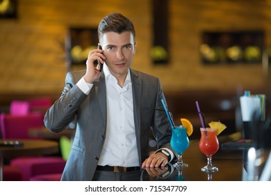 Young businessman in a cafe bar talking on a smart phone