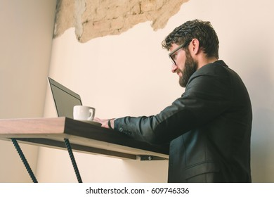 Young businessman at the cafe using laptop