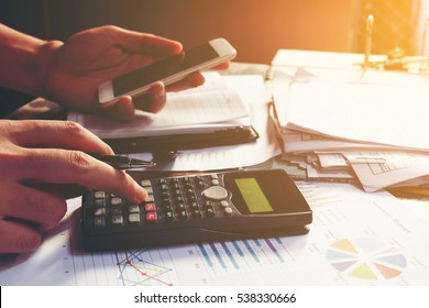Young businessman calculating about cost and using smartphone searching data in office.