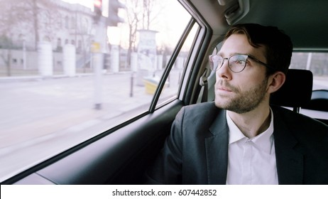 Young Businessman in the Car Using a Tablet Computer