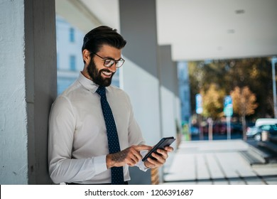 Young businessman carries out its corporate business outside and talking on the phone.