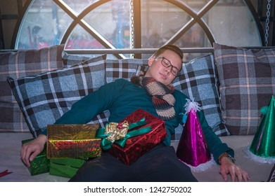 Young businessman celebrating Christmas party at home sleeping on sofa.Businessman with party hat sleeping at office after Christmas party and happy new year.