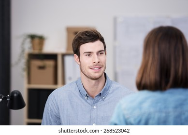 Young businessman chatting to colleague in the office, view over her shoulder of his face