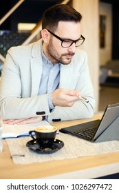 Young businessman checking daily agenda on a tablet while working in a modern coffee shop. Work anywhere concept