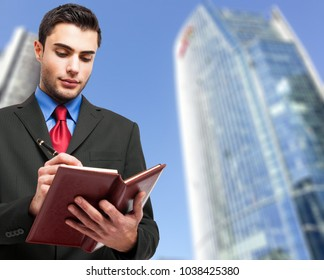 Young businessman checking his agenda outdoor
