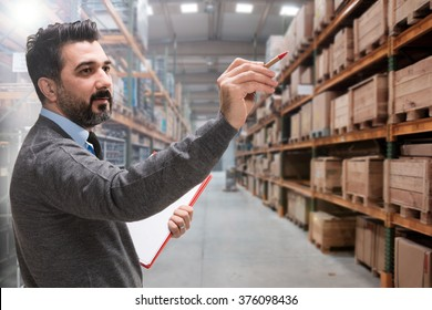 Young businessman checking inventory in a large warehouse.