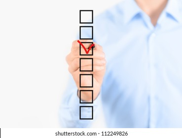 Young businessman checking mark on checklist with marker. Isolated on white.