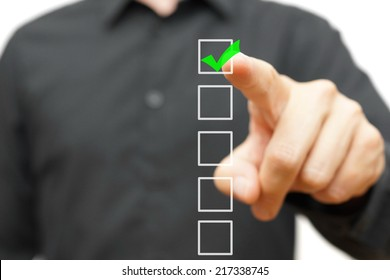Young businessman checking mark on checklist with marker.