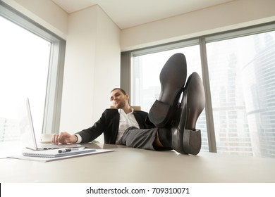 Young businessman chilling and relaxing at workplace in modern office. He is sitting with legs up on desk and looking at laptop screen. Taking a break, done with project, being lazy at work concept.