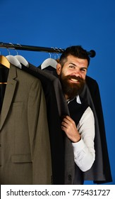 Young businessman choosing suit from row of suits in suit shop. Man with beard and smiling face hides behind classic jackets. Fashion victim concept