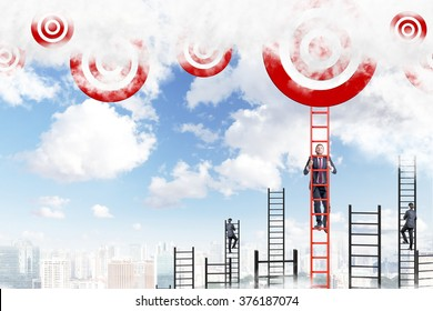 A young businessman climbing a red ladder to the sky, two men climbing other ladders. Red targets at the top. Blue sky and city at the background. Concept of career growth.