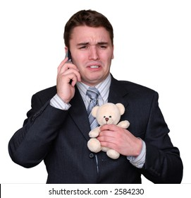 Young businessman clutching a small teddy bear, crying and talking on a cell phone. Isolated on white.