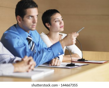 Young businessman with colleagues giving presentation in conference room