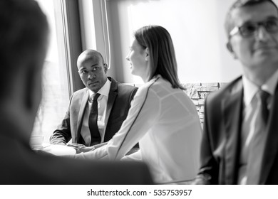 Young businessman with colleagues in office cafeteria