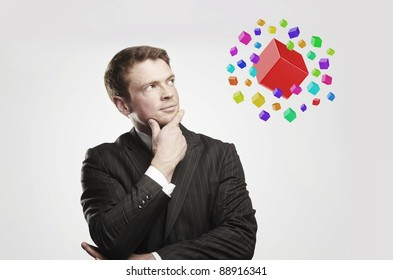 Young  businessman with colored boxes. On a gray background