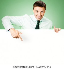 Young businessman in confident shirt and tie, showing blank sign board, with empty copy space place for some text, advertising or slogan, over green background