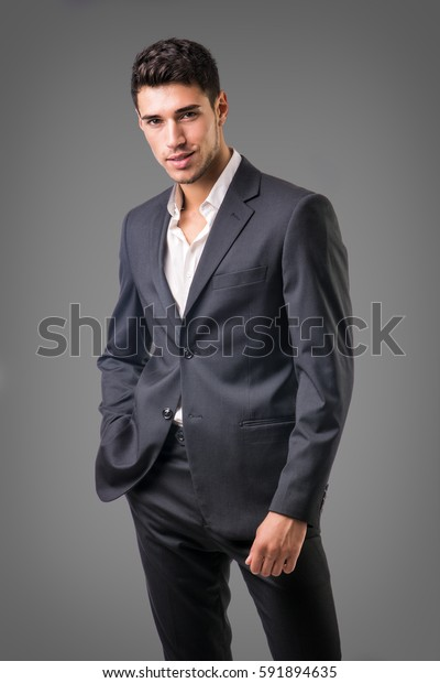 Young businessman confidently posing in front of camera, wearing business suit without neck-tie, with shirt open on neck, on dark background