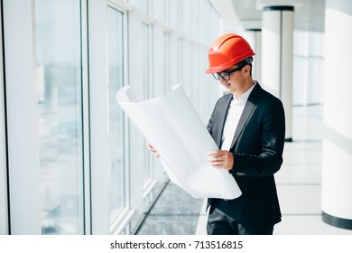 Young businessman in construction helmet with blueprints