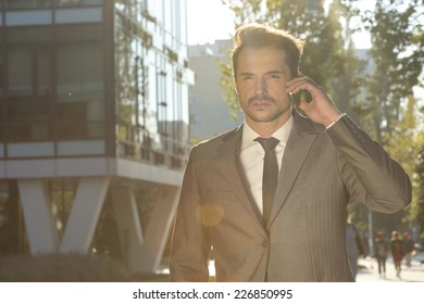 Young businessman conversing on cell phone outdoors