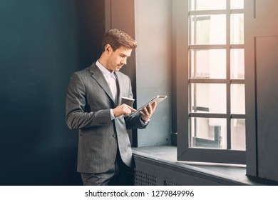 Young businessman in a corporate office reading information on his digital tablet while holding a cup of coffee in front of large windows with gentle sunflare